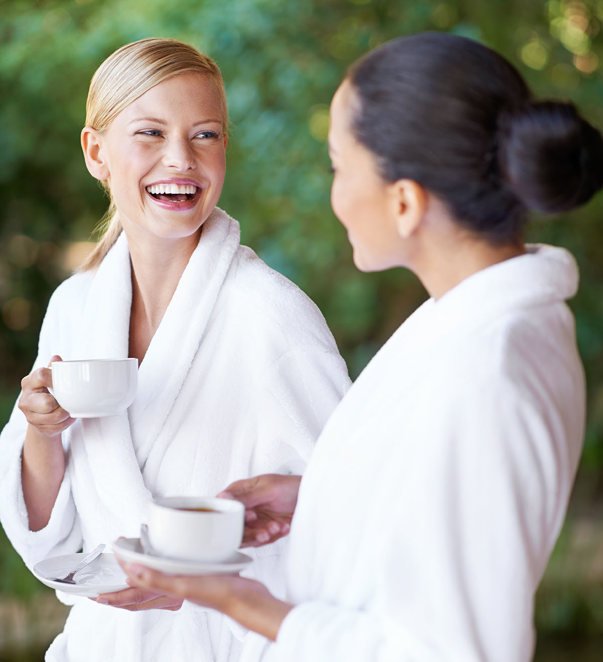 Two young women having coffee in their bathrobes at the spa
